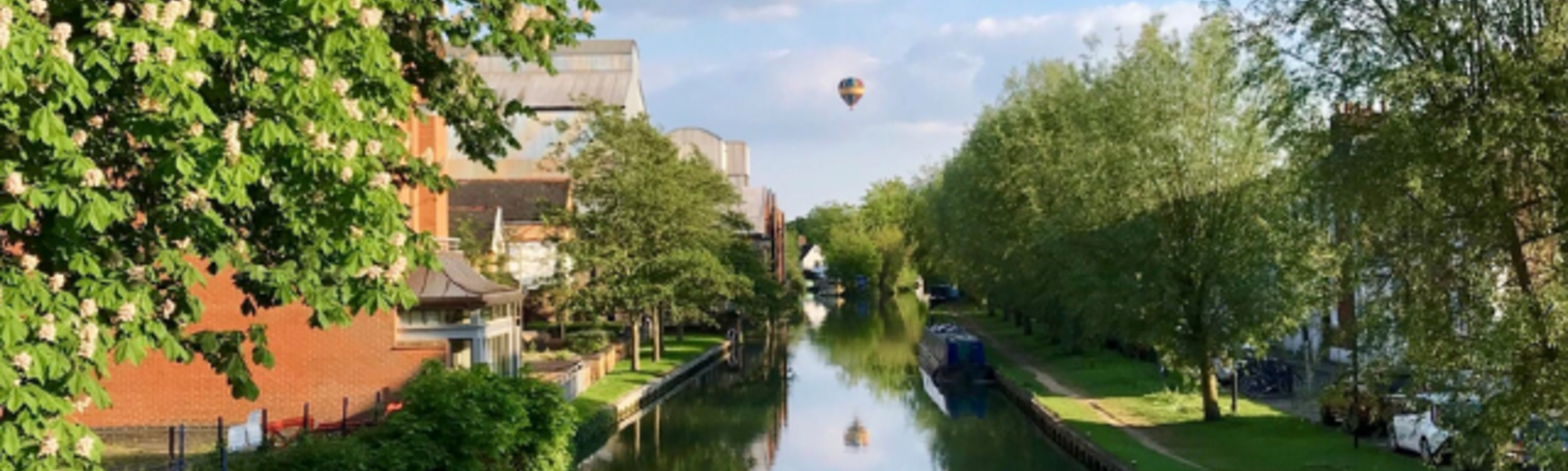 Photo of the Oxford canal with a hot air ballon in the sky above
