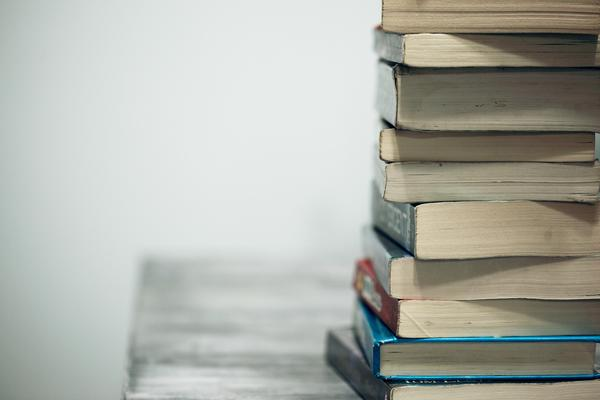 Photo of a stack of books on a table against a white background
