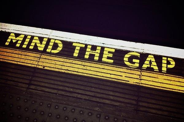 Photo of the edge of a train platform with 'MIND THE GAP' painted in yellow