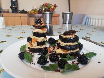 Photo of an aubergine, blackberry and mint dish on a dining table