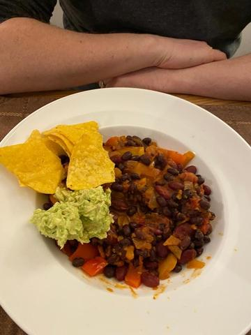 Photo of a bowl of vegan bean chilli with tortilla chips and guacamole
