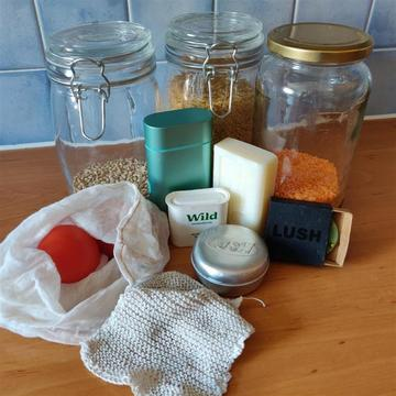 Image of grouped of items including, soap bars, jars of dry goods and reusable bags and tins.