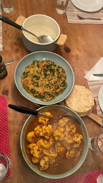 Photo of bowls of lentil dahl and curried cauliflower on a table