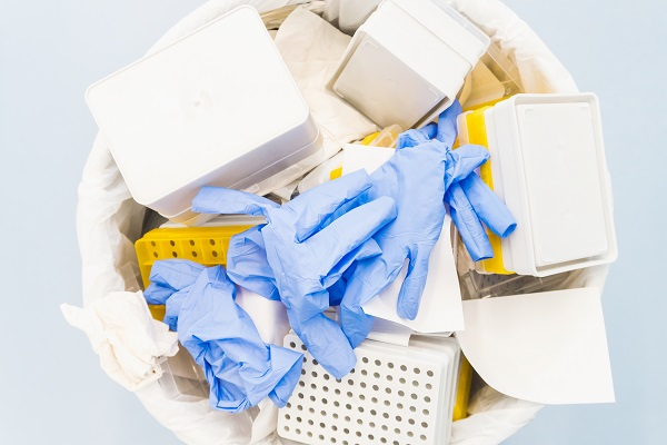 Birdseye photo of blue gloves and other lab waste in a bin, blue background